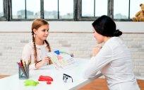 Dziewczynka z kobietą przy biurku. Dziewczynka pokazuje namalowany rysunek kobiecie.